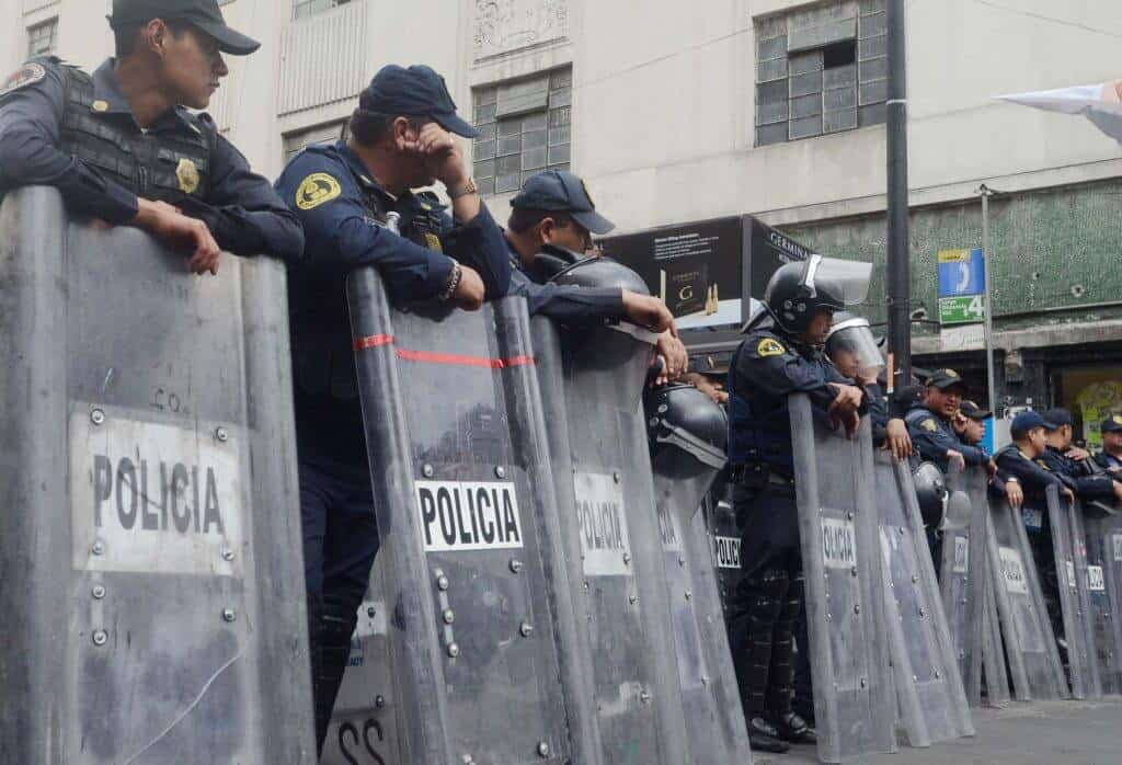 Mexico City Police stand along Balderas Ave during the 43 missing student march in Mexico City on May 26th 2015 .