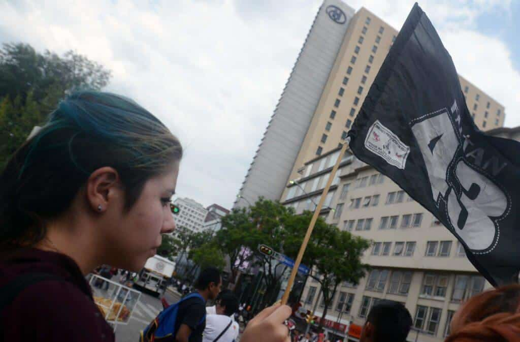 Sara Eslava, 20, of Mexico City waves a flag in support of the 43 missing student during a march in Mexico City on May 26th 2015.